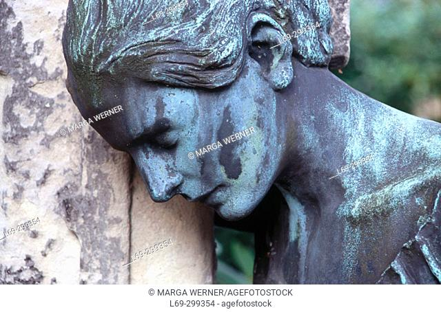 Mourning lady at gravestone. Ohlsdorf, Hamburg's largest park and cemetery, Germany
