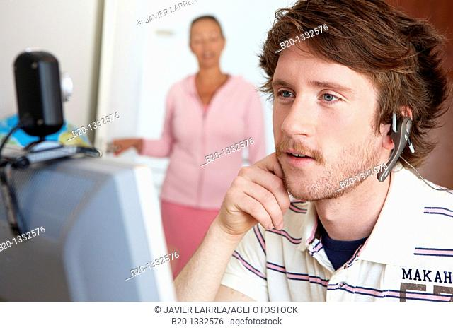 Mother calling son who is looking at computer in his room