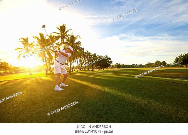 Caucasian golfer hitting ball on golf course