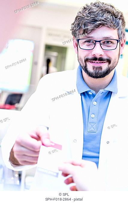 Optometrist handing receipt to woman