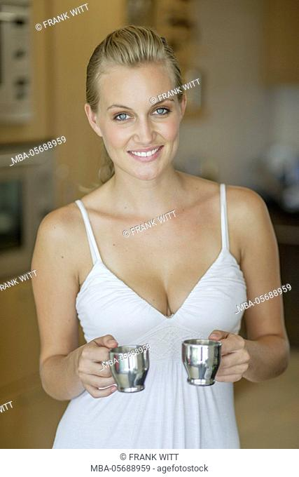 Young woman in the white dress is holding two cups of espresso in the kitchen