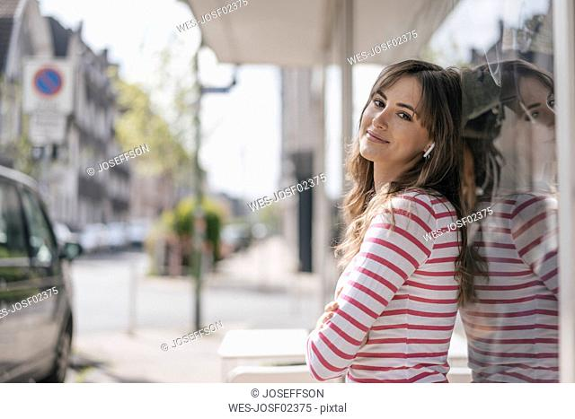 Young woman with earbuds, listening music in the city