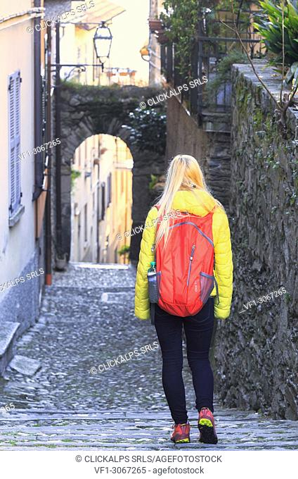 A girl walks in a street of Rezzonico, Como Lake, Lombardy, Italy, Europe