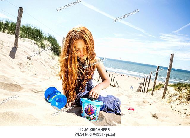 Netherlands, Zandvoort, redheaded girl playing on the beach