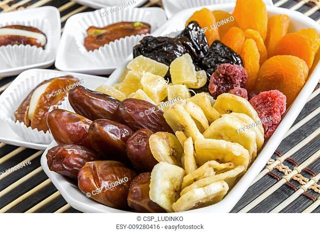 various dry fruits in a bowl and dry dates stuffed