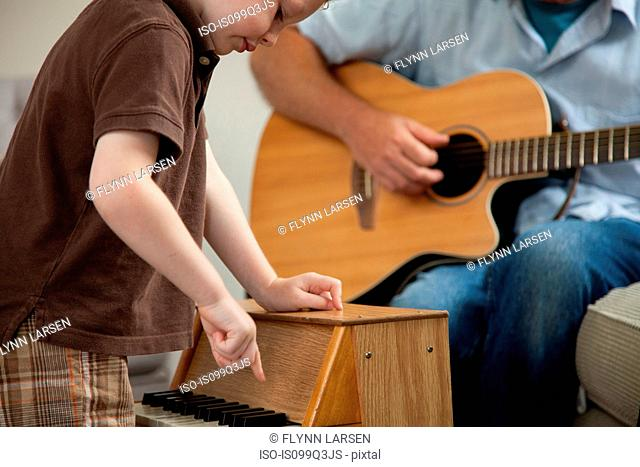 Boy playing little piano as man plays guitar