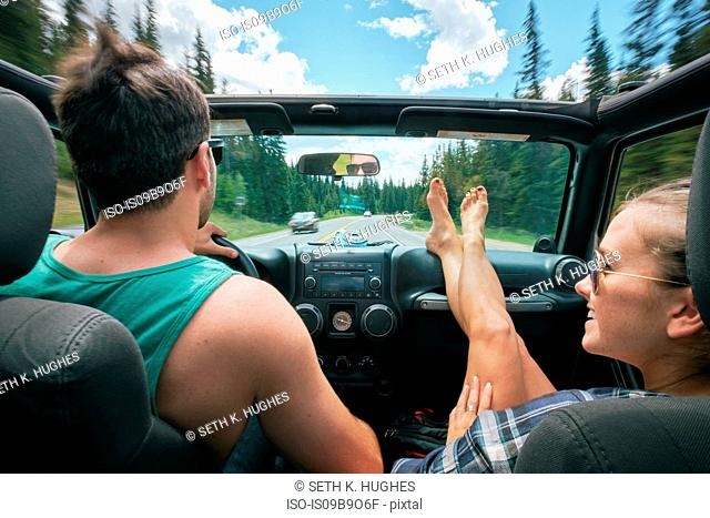 Young woman with feet up driving on road trip with boyfriend, Breckenridge, Colorado, USA