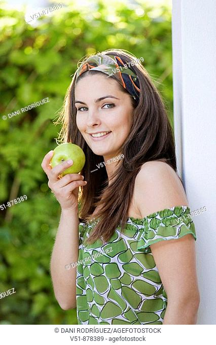 Woman with an apple outdoor looking at camera