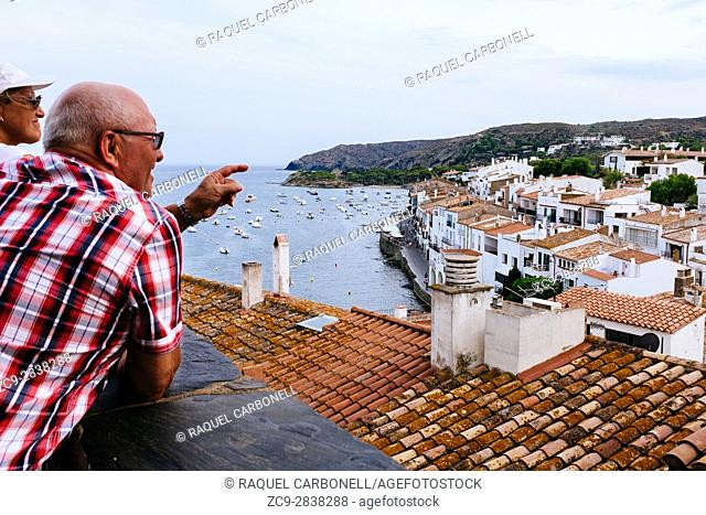 Couple of tourists enjoying elevated view of white town by sea. Cadaqués, Alt Amporda, Gerona, Catalonia, France