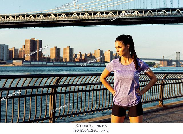 Young female runner looking out in front of Manhattan bridge, New York, USA