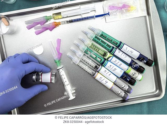 Syringes of insulin medication next to medicine vials prepared in hospital, conceptual image, horizontal composition