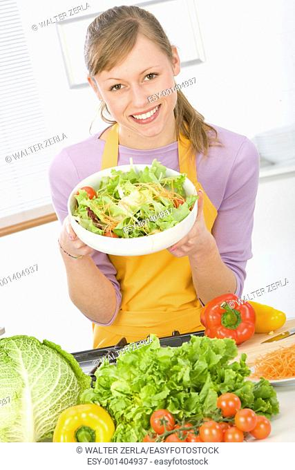 Beautiful young woman making vegetarian vegetable salad