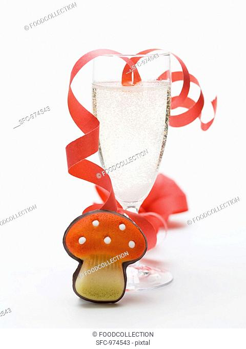 Glass of sparkling wine, paper streamer, marzipan fly agaric