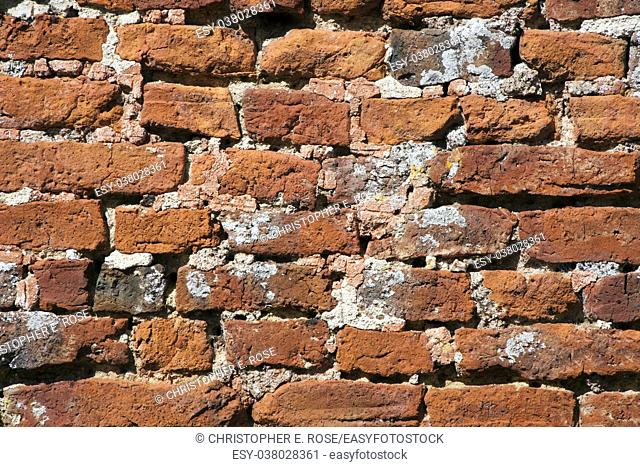 Very old weathered, damaged, badly repaired hand made red brick wall close up