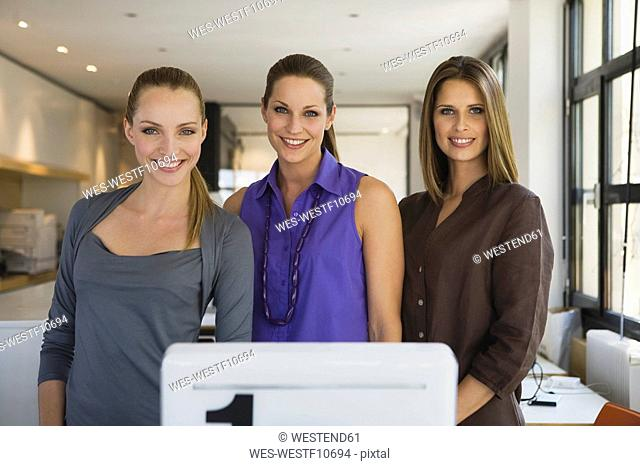Young women in office, smiling, portrait