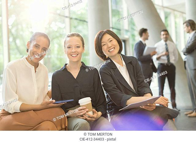 Portrait smiling businesswomen meeting in office lobby