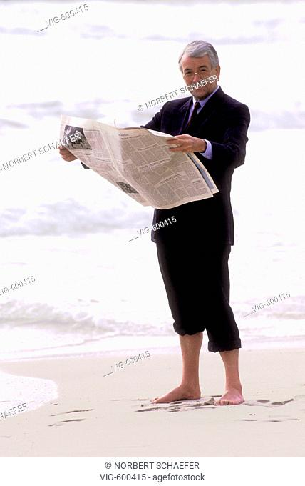 Man in a suit standing on the seafront and reading a newspaper. - 09/01/2008