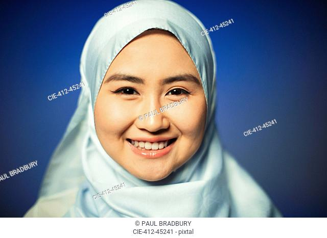 Close up portrait smiling, confident young woman wearing blue silk hijab