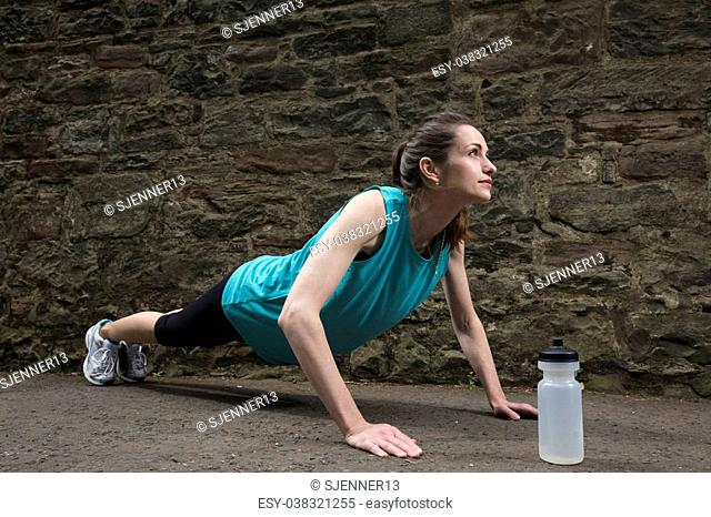Young and fit sporty woman doing push-ups during outdoor training session. Action and healthy lifestyle concept