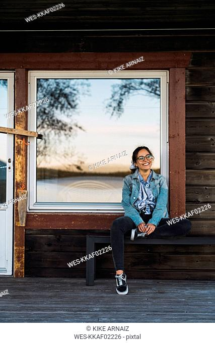 Happy young woman sitting on veranda of a wooden house