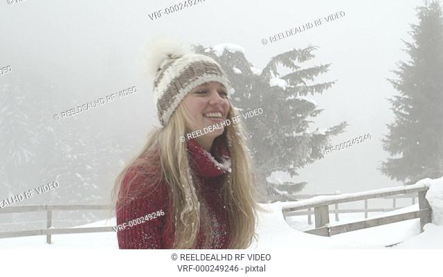 Young woman enjoying in winter with throwing snow up