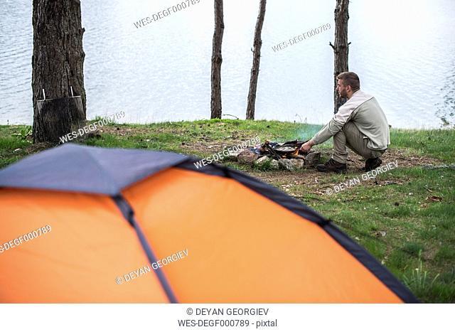 Man frying at camp fire at shore of a lake