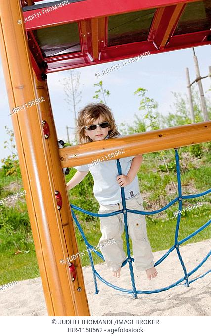 Boy, three years old, with sunglasses, climbing in the playground
