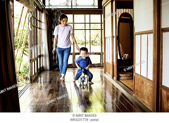 Smiling Japanese woman and little boy on a tricycle on porch of traditional Japanese house