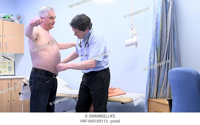 WS Male doctor measuring male patient's waist