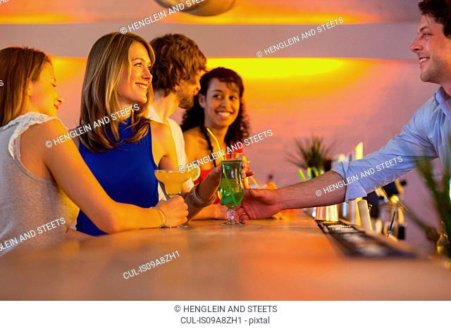 Group of friends ordering cocktails in bar