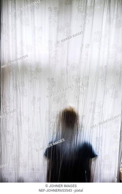 A boy behind a curtain