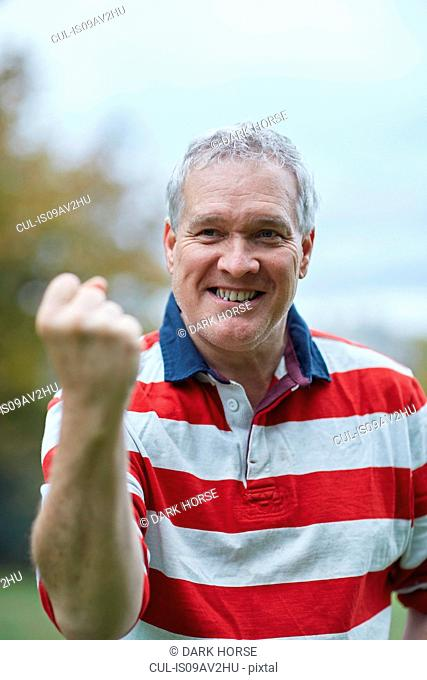 Portrait of mature man making a fist in celebration whilst training