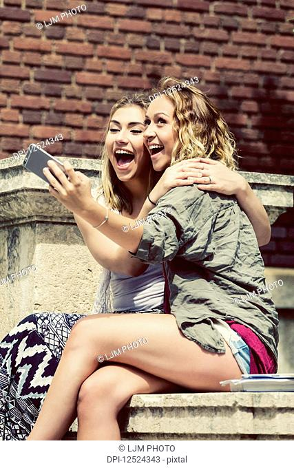 Two female university students sitting together on the campus, being silly and taking a self-portrait with their smart phone; Edmonton, Alberta, Canada