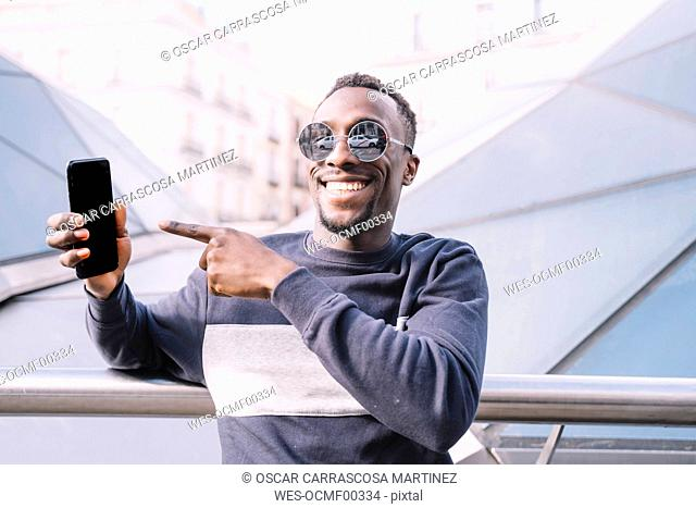 Spain, Madrid, portrait of happy young man showing his mobile phone