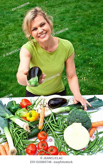 Cute blond with vegetables girl shot outdoor with grass in background