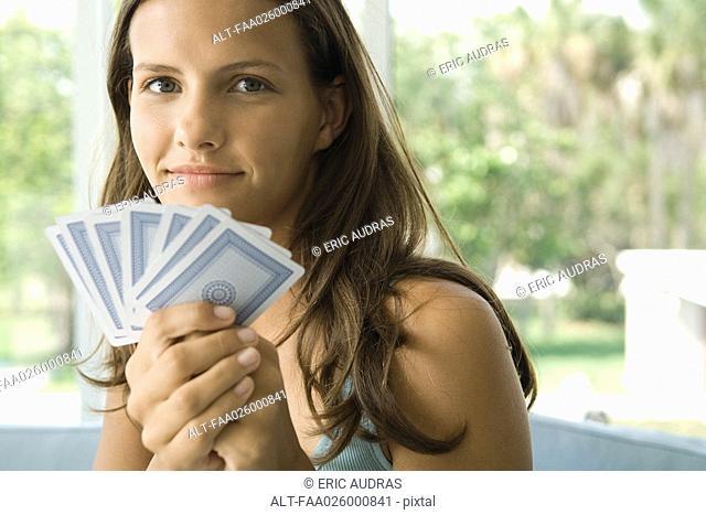 Teenage girl holding up cards, smiling at camera, close-up