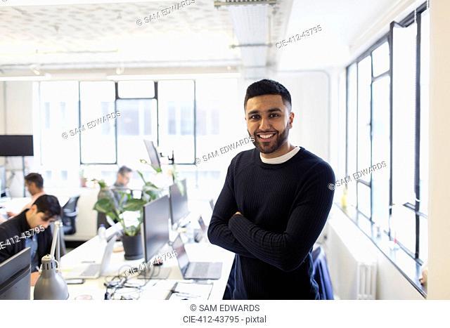 Portrait smiling, confident businessman in open plan office
