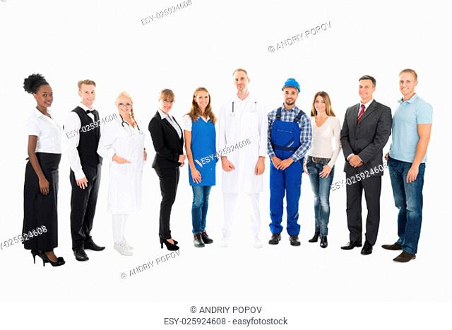 Full length portrait of people with various occupations standing in row against white background