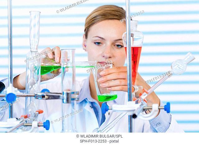 Female chemist pouring chemicals into glassware in laboratory