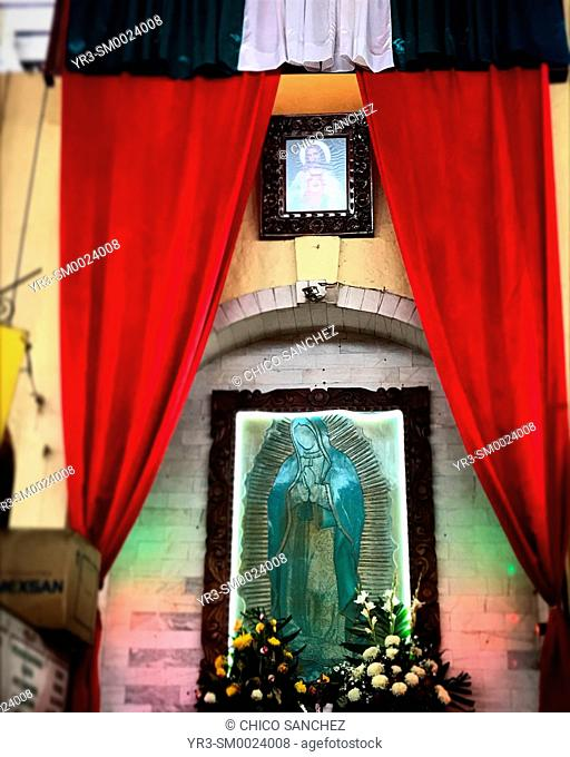 A Mexican flag, a picture of Jesus Christ and an image of Our Lady of Guadalupe decorate a market in Dolores Hidalgo, Guanajuato, Mexico