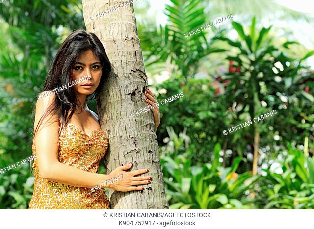Sexy young woman, standing at a tree trunk, Indonesia, Asia