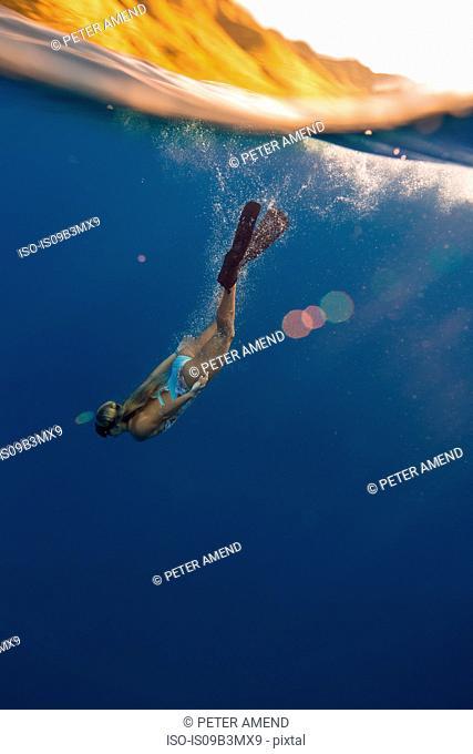 Woman wearing flippers swimming underwater, Oahu, Hawaii, USA