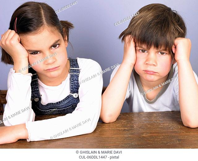 Girl and boy annoyed at their desk