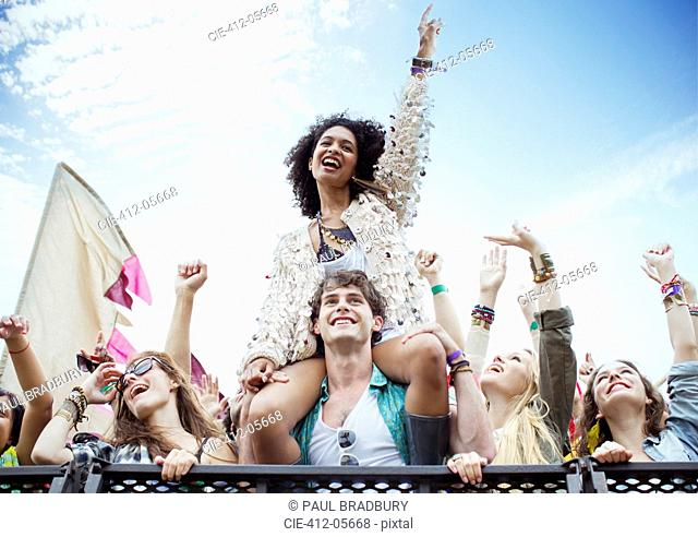 Cheering woman on manÍs shoulders at music festival