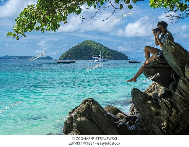 Woman sitting on the rock with camera doing pictures