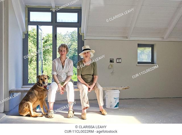 Older mother and daughter sitting on plank with dog in newly built house