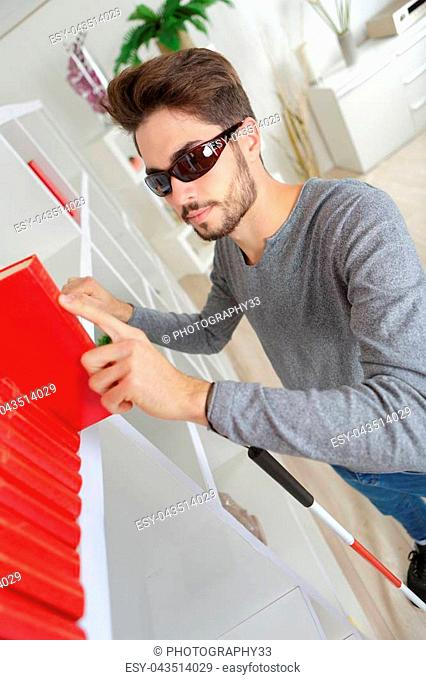 Blind man reading braille on spine of book