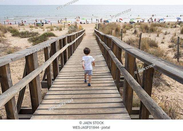 Spain, Huelva, back view of little boy running to the beach on boardwalk