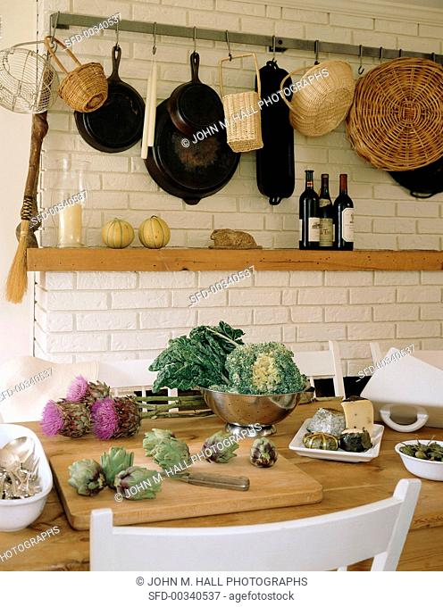 A culinary arrangement featuring fresh vegetables, hanging baskets and pans