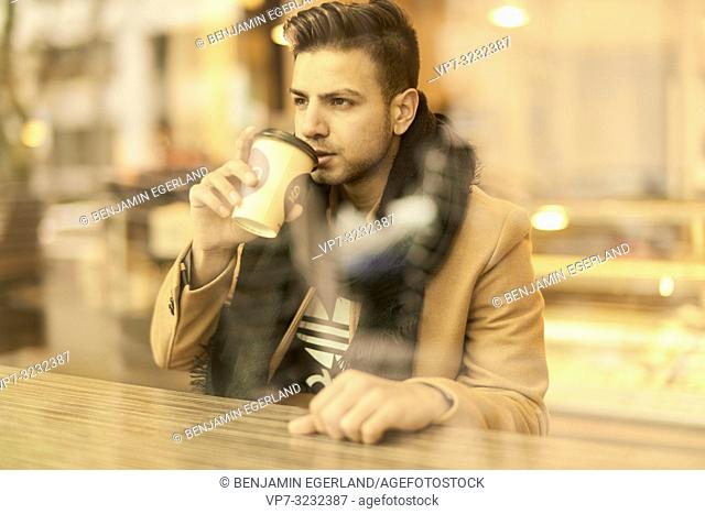 young man behind window drinking coffee from plastic cup in café in Munich, Germany